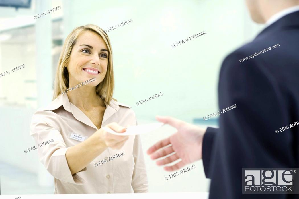 Stock Photo: Woman smiling, handing document to businessman.