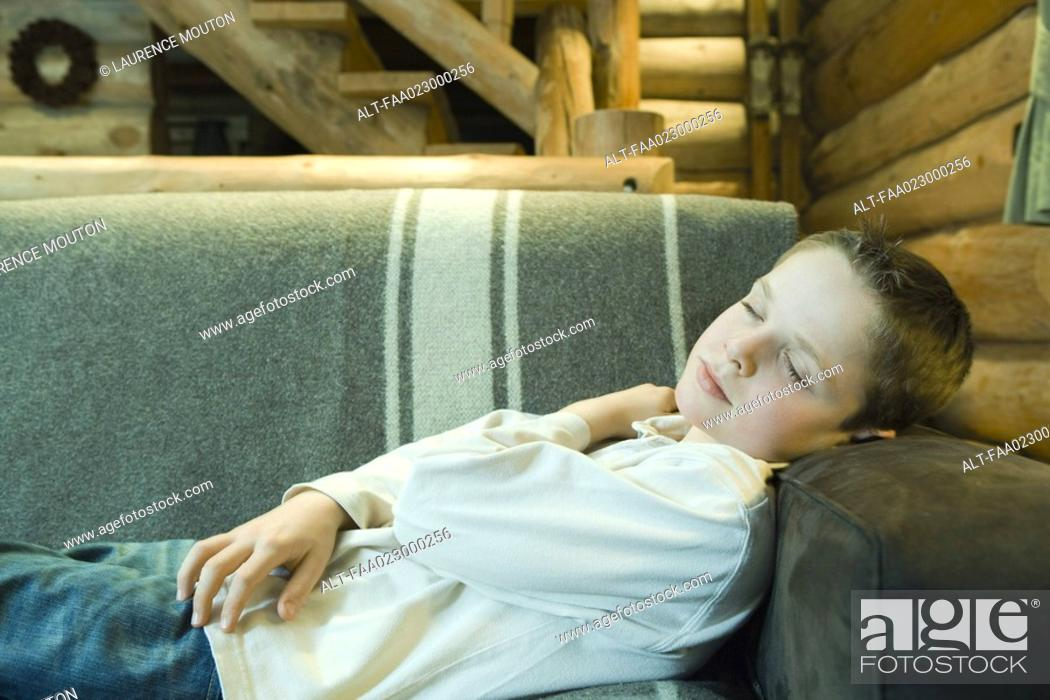 Stock Photo: Preteen boy falling asleep on couch.