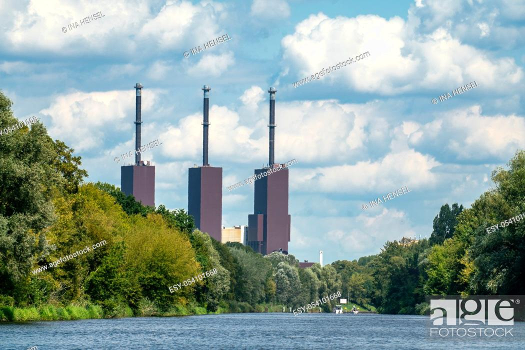 Stock Photo: Teltow, Germany - august 14, 2019: The Berlin Lichterfelde power station with its three chimneys looking over the water of the Teltow canal.