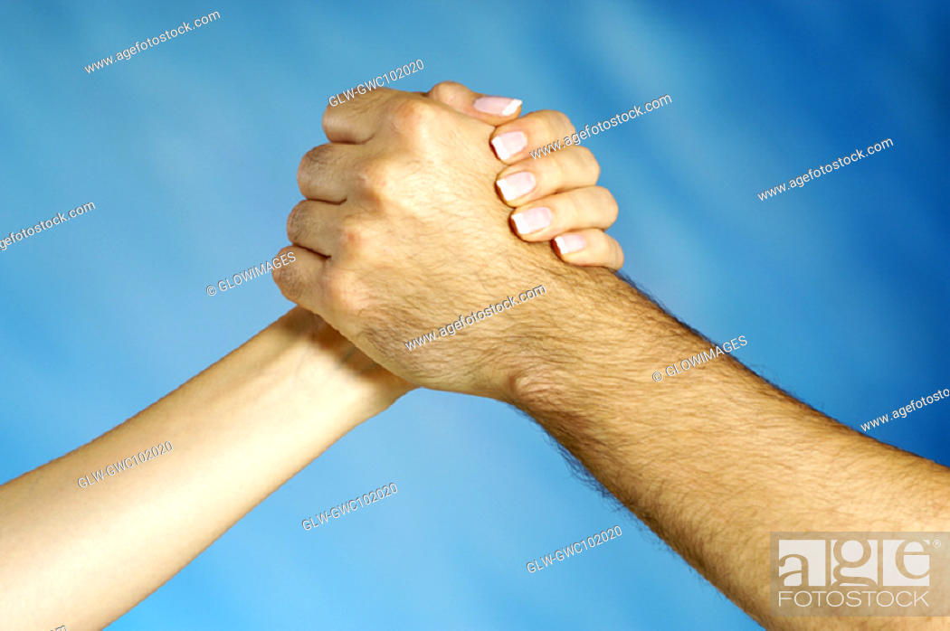 Stock Photo: Close-up of a man and a woman arm wrestling.