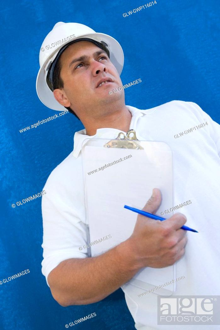 Stock Photo: Low angle view of a male construction worker holding a clipboard and a pen.
