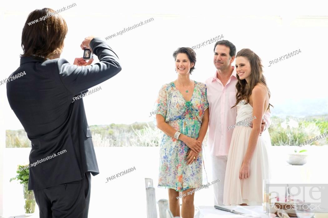 Stock Photo: Groom taking a picture of bride with her parents at a wedding party.