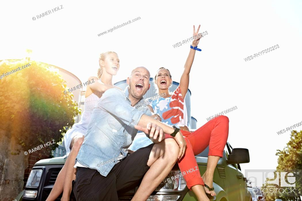 Stock Photo: Germany, Cologne, Man and women sitting on car.