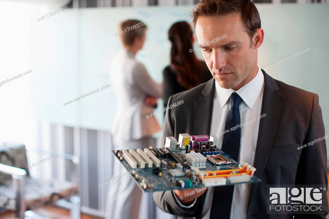 Stock Photo: Businessman looking at motherboard in office.