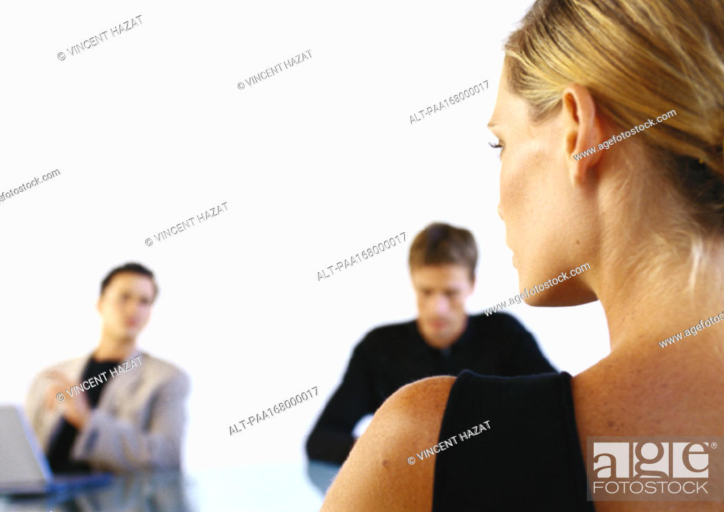 Stock Photo: Woman sitting across from two men in office, rear view.