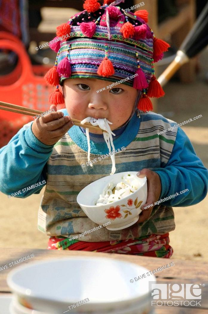 Imagen: Hmong boy stuffing his face with noodles at market in Tam Duong near Sapa Vietnam.