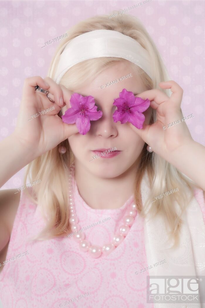 Stock Photo: a girl in 60s style with two purple flowers in front of her eyes.