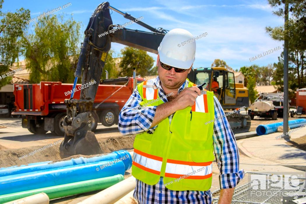 Stock Photo: Caucasian construction worker listening to walkie-talkie.