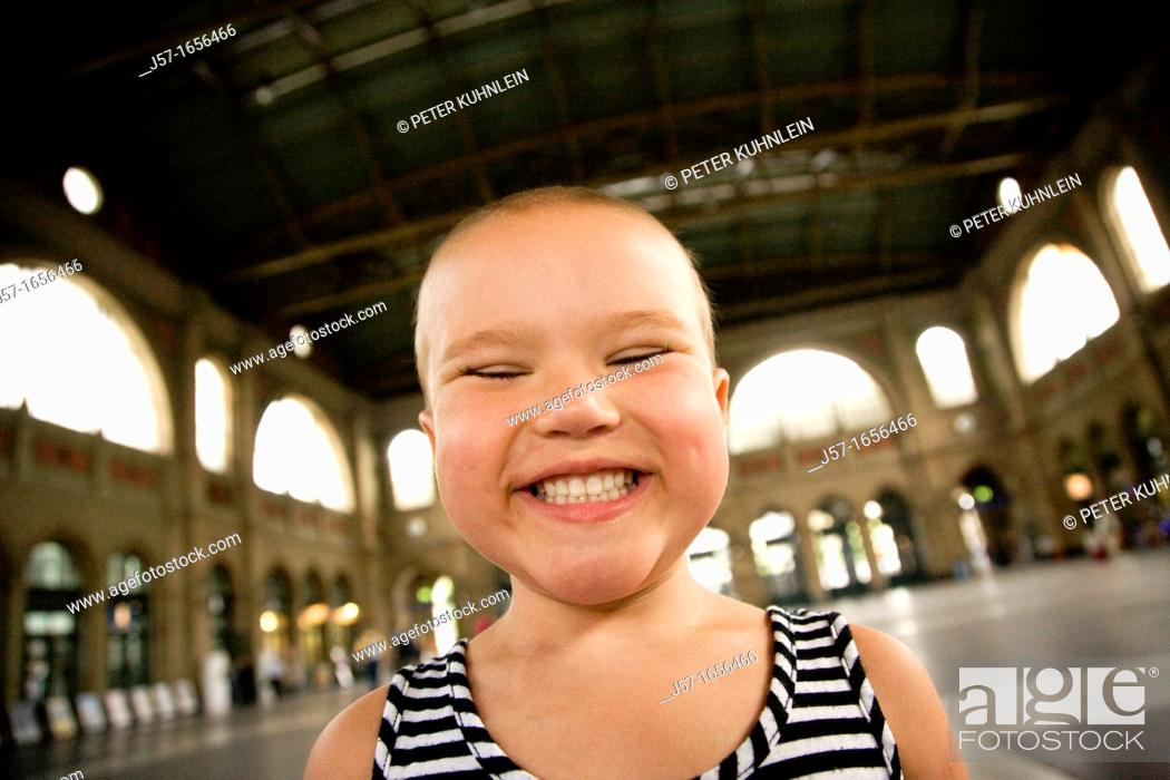 Stock Photo: Young bald girl with pediatric cancer Leukimia looking happy and smiling in the Zurich train station, Switzerland.
