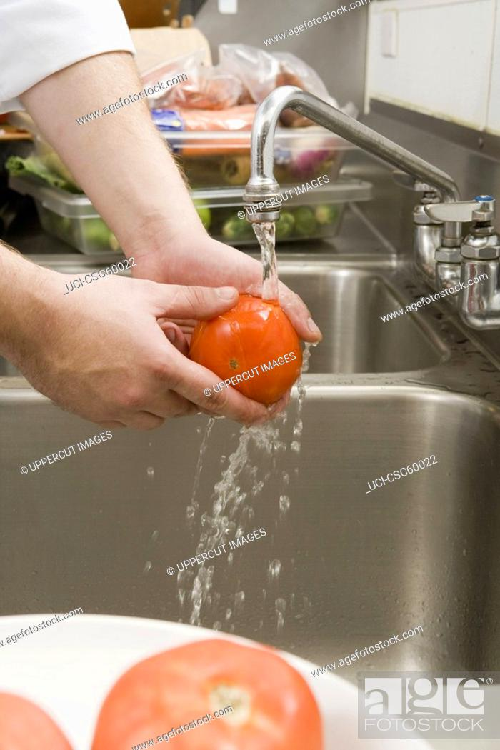 Stock Photo: Man washing tomato.