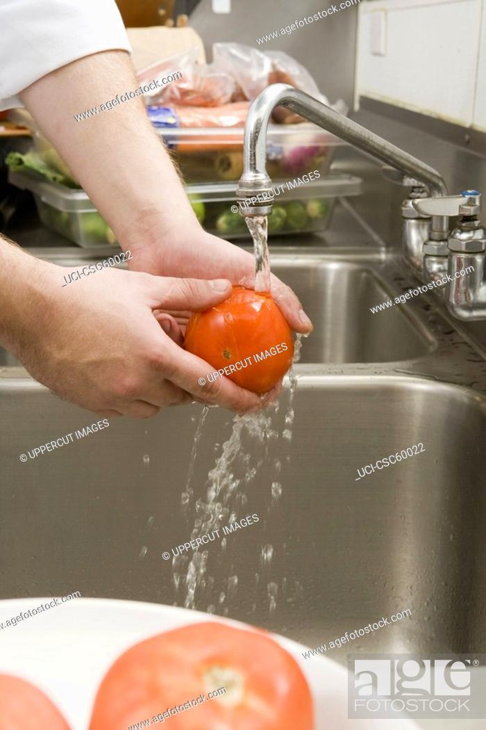 Stock Photo: Man washing tomato.
