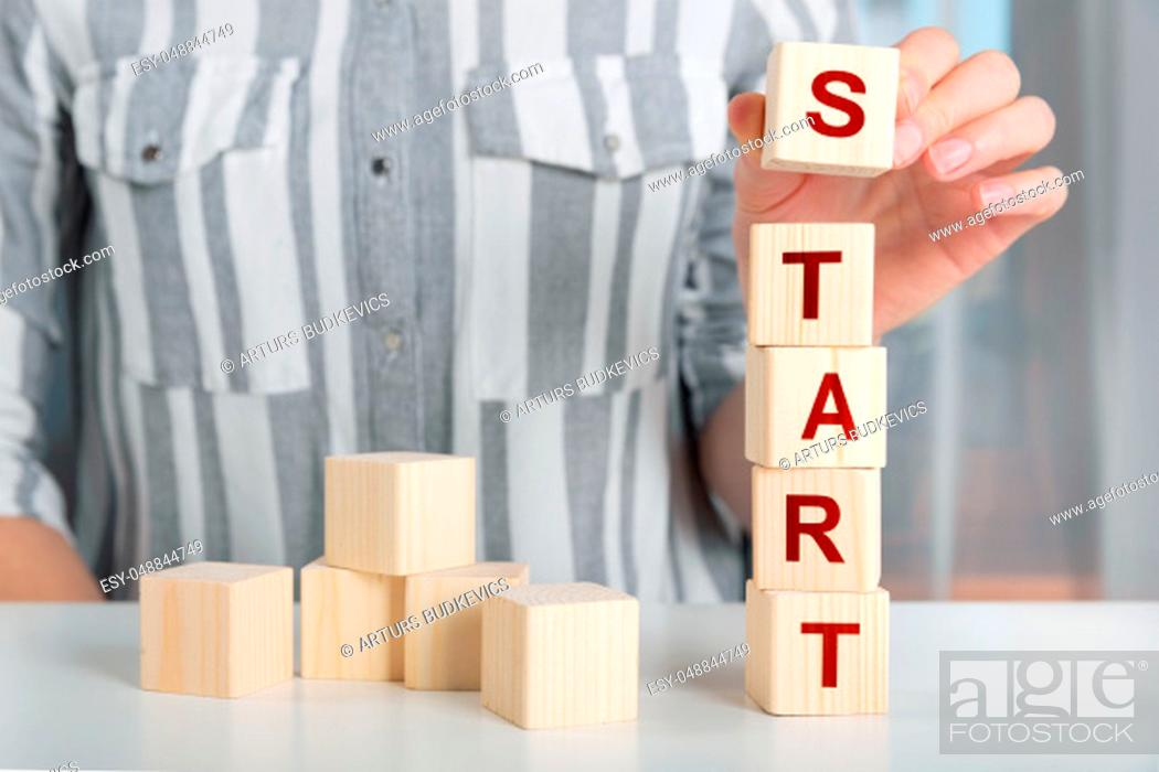Stock Photo: Hand of female putting wood cube block with words START UP on table. Start up concept.