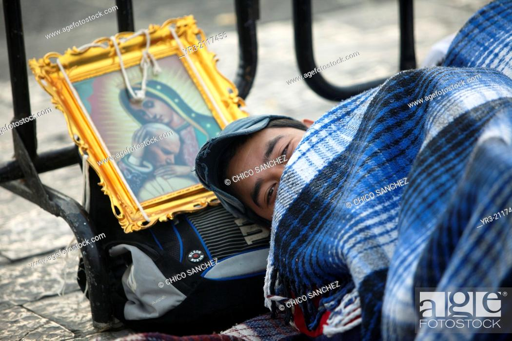 Stock Photo: A pilgrim sleeps close to an image of the Virgin of Guadalupe and Pope John Paul II at the pilgrimage to Our Lady of Guadalupe Basilica in Mexico City, Mexico.