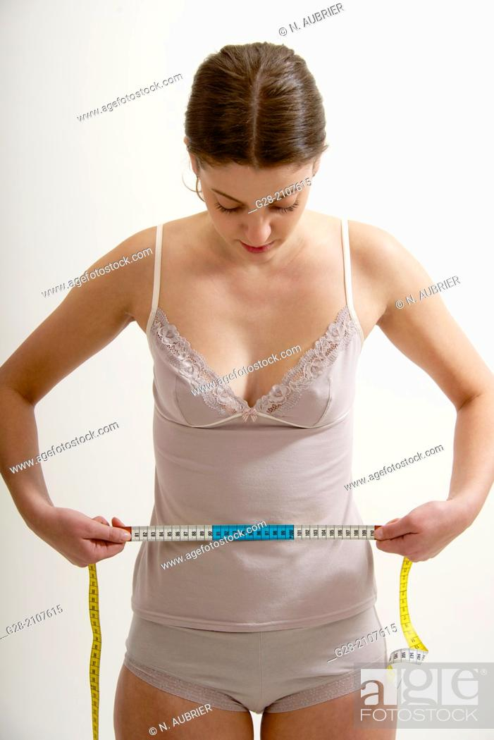 Stock Photo: Young beautiful woman in pink underwear, measuring her waistline with a measuring tape.