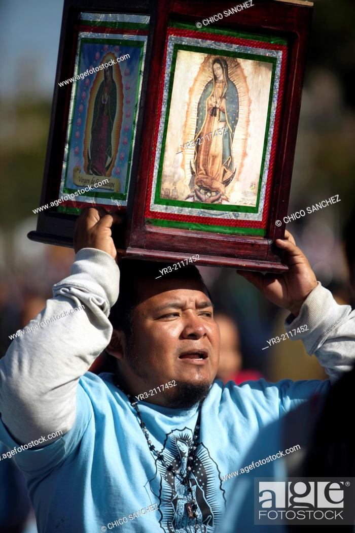 Stock Photo: A pilgrim holds an image of the Virgin of Guadalupe as the sun rises at dawn at the pilgrimage to Our Lady of Guadalupe Basilica in Mexico City, Mexico.