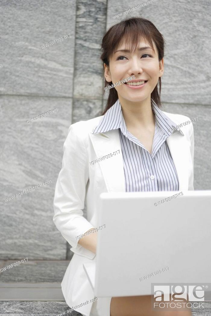 Stock Photo: A woman working on her laptop smiles at someone.