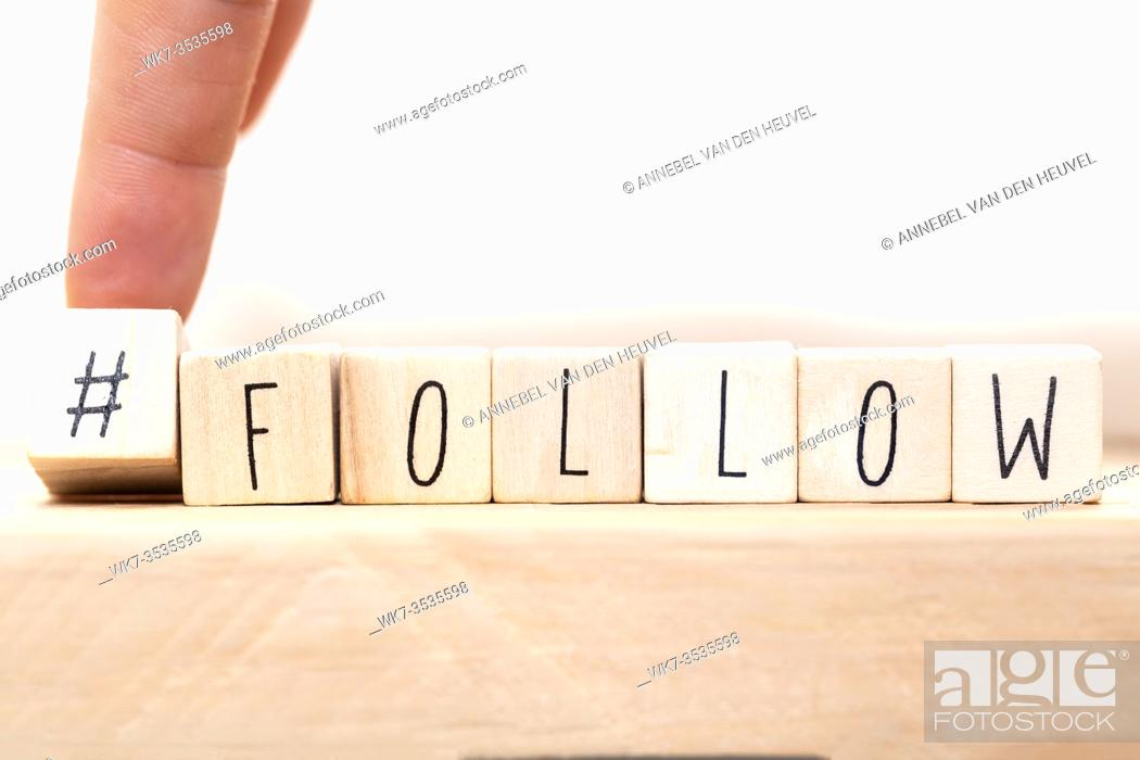 Stock Photo: Follow sign made of cubes on a wooden table with Hashtag near white background, socialmedia concept close-up.
