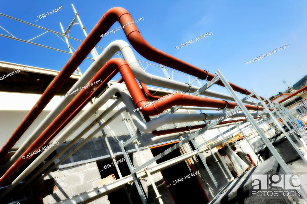 Stock Photo: Set of pipes on the roof of a building.
