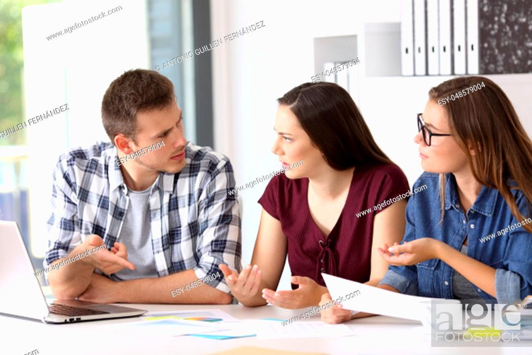 Stock Photo: Three employees having a job conversation sitting in a desktop at office.