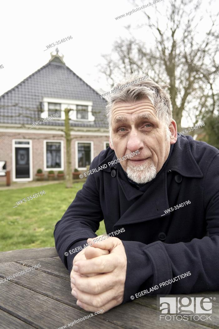 Stock Photo: senior man in front of home in Friesland, Netherlands.