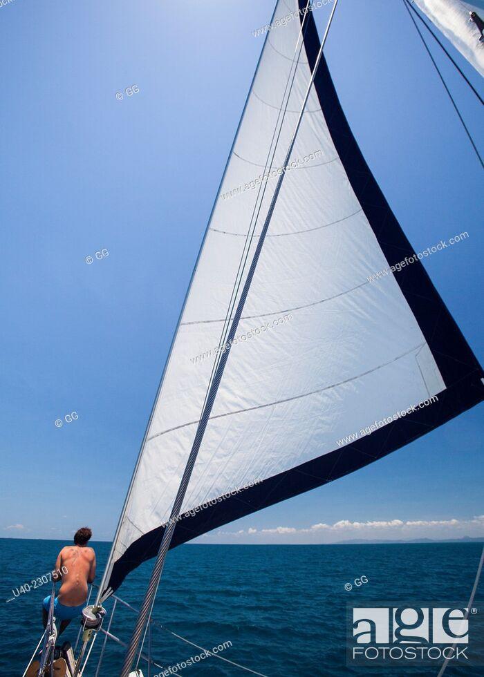 Stock Photo: Man sitting on bow of sailboat, Belize.