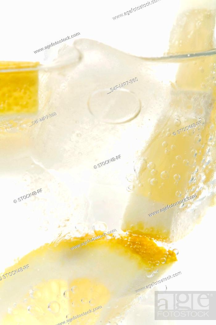 Stock Photo: Mineral water with ice cubes and lemon slices.