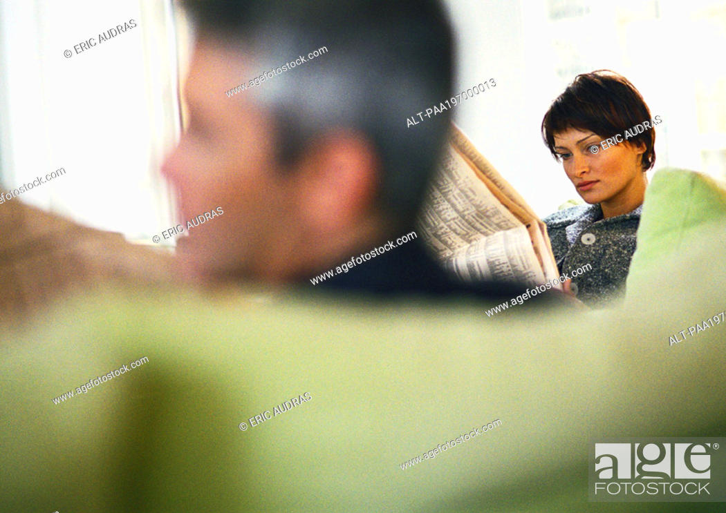 Stock Photo: Businessman and businesswoman reading newspaper, blurred foreground.