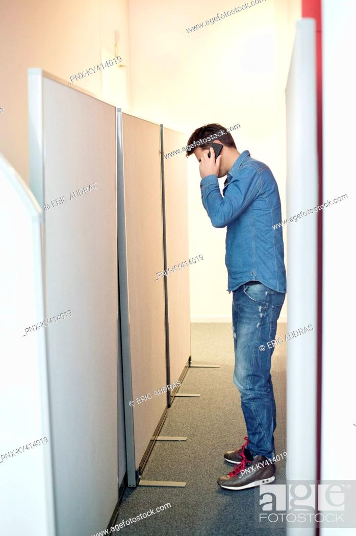 Stock Photo: Businessman talking on a mobile phone in an office corridor.