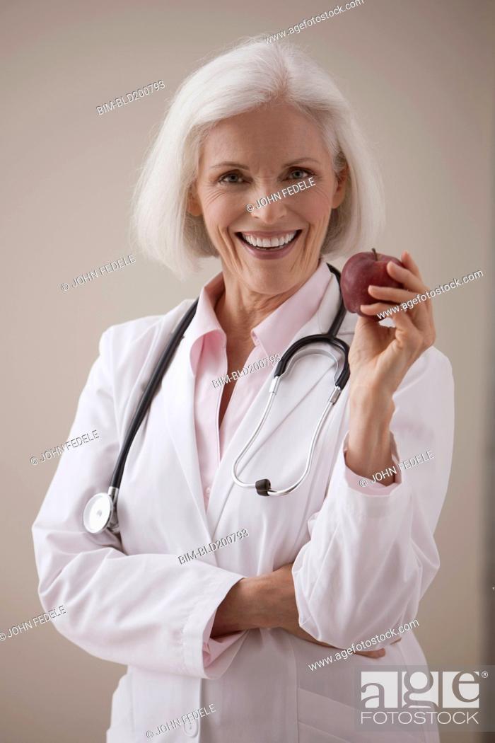 Imagen: Caucasian doctor holding red apple.
