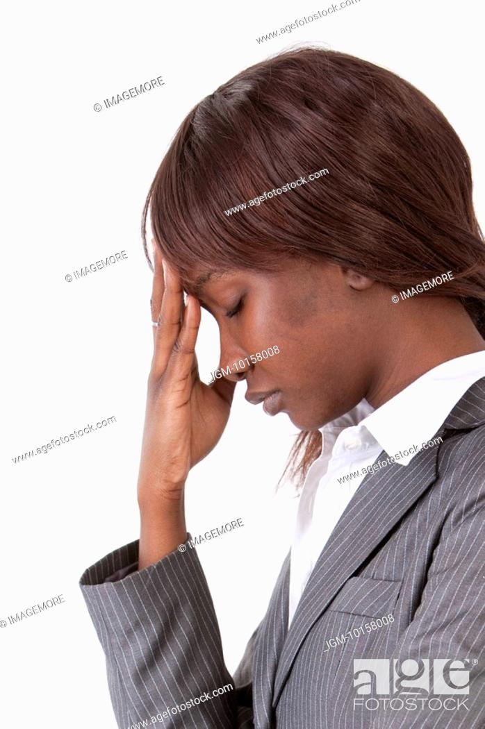 Stock Photo: Young woman looking down with eyes closed and thinking with head in hands.