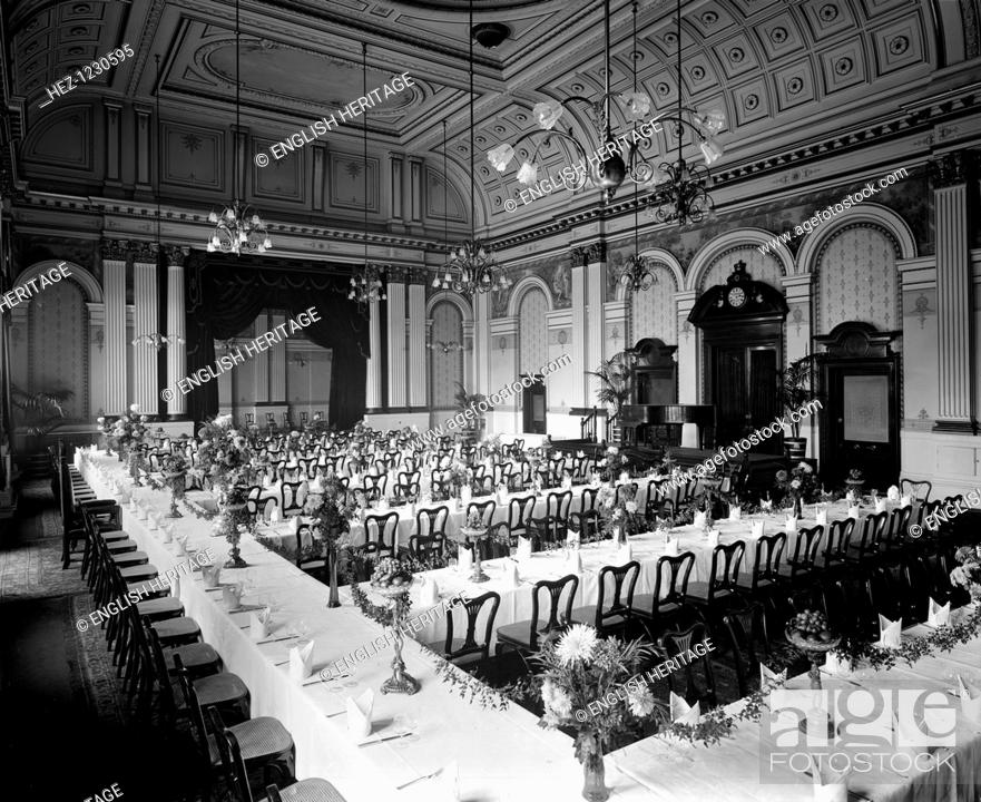 Tables laid out for a formal dinner in the grand hall of the