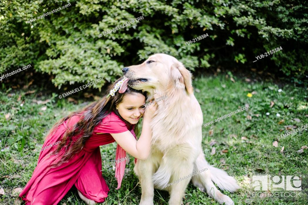 Stock Photo: Portrait of little girl with crown of daisies and Golden Retriever dog.