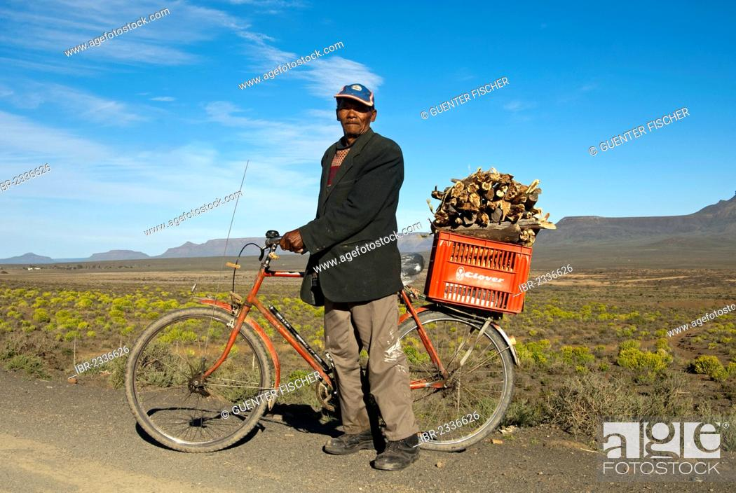Stock Photo: Local man with a bicycle and a box of firewood on the luggage rack, near Calvinia, Northern Cape Province, South Africa, Africa.