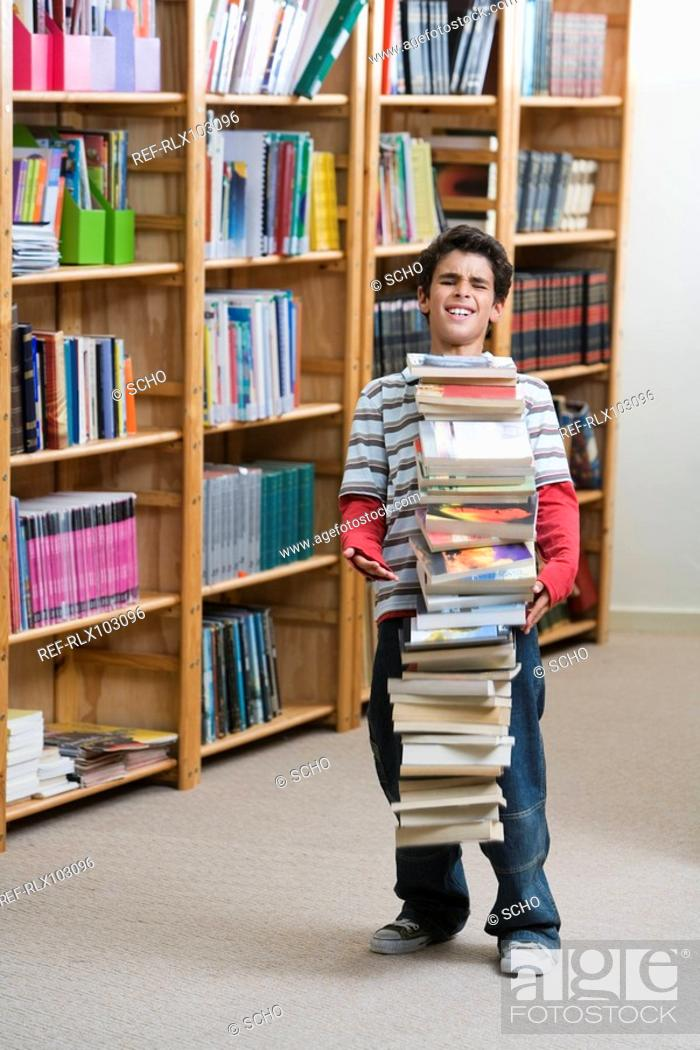 Stock Photo: Boy 10-13 in library, dropping a big pile of school books.