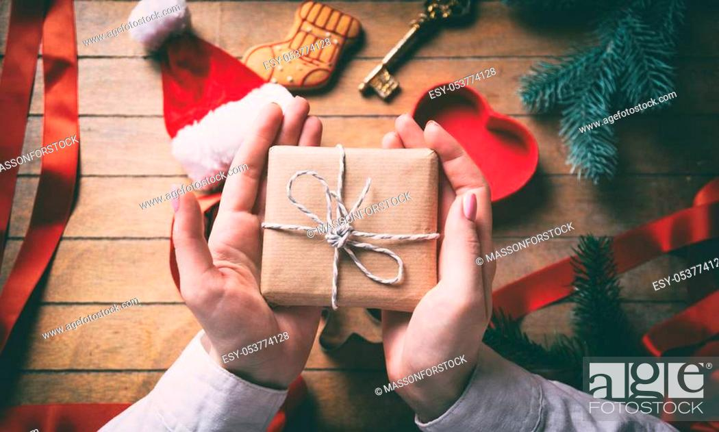Stock Photo: Young woman hands wrapping christmas gifts and cookies on wooden background, Photo in old color image style.