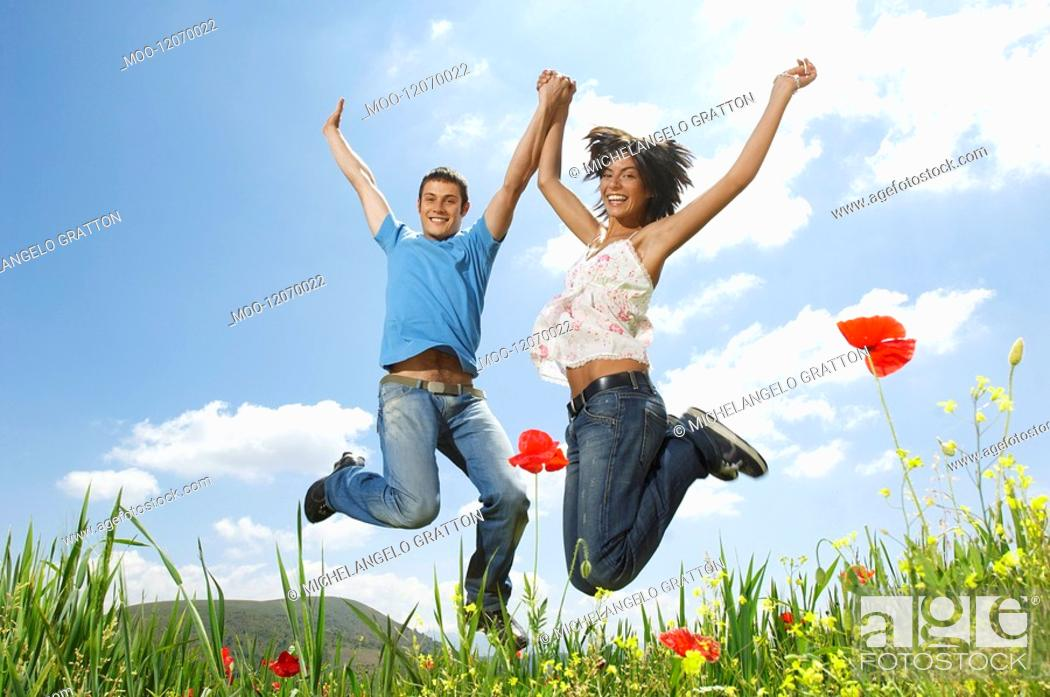 Stock Photo: Young couple jumping for joy in mountain meadow portrait low angle view.