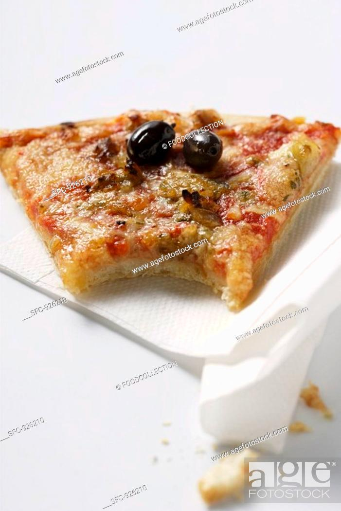 Stock Photo: Piece of pizza with tuna and olives, a bite taken.