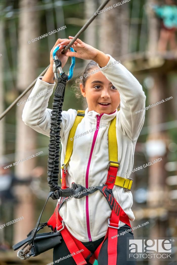 Photo de stock: Young climber having fun in adventure natural park outdoor - Young happy people doing extreme sport in weekend, holiday and vacation concept.