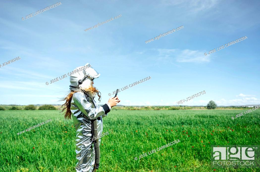 Stock Photo: Side view of girl in space suit using smart phone while standing on grass.