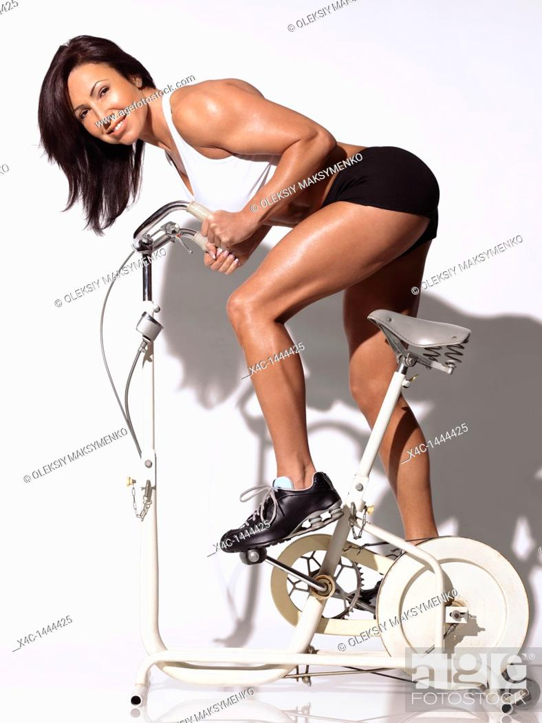 Stock Photo: Fitness woman in her forties on an exercise bike.