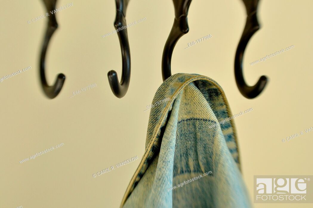 Stock Photo: cloakroom, black hooks and hanging denim jacket. Shot with LensBaby for selective focus.