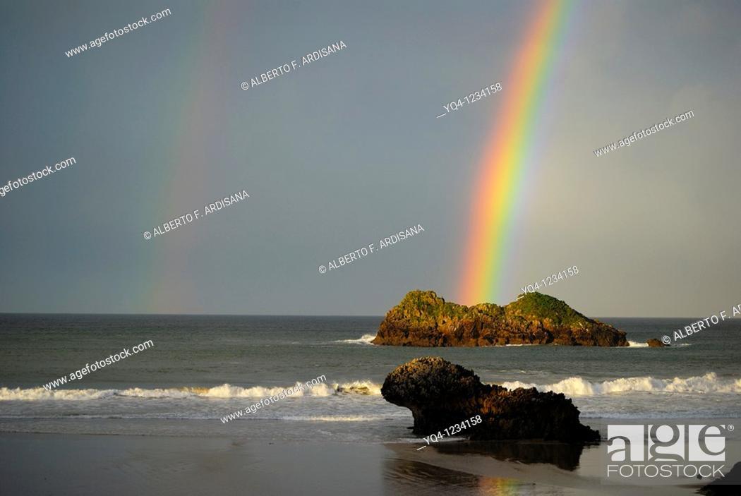 Stock Photo: Rainbow over the beach Celorio Llanes, Asturias.