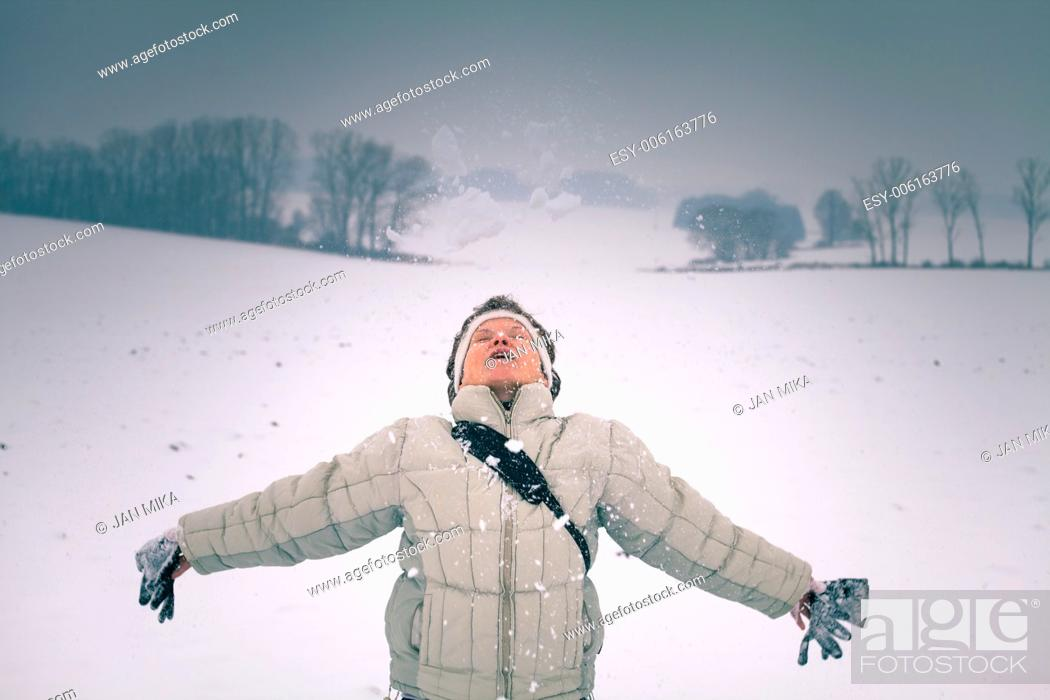 Stock Photo: Ecstatic middle aged woman enjoying snow in winter.