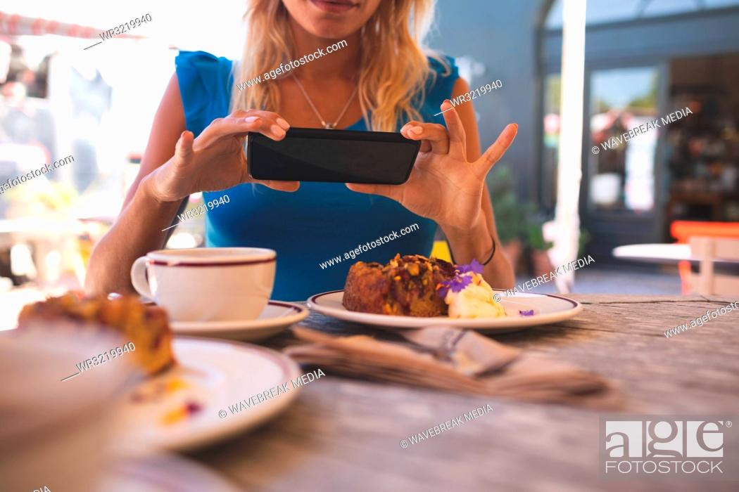 Stock Photo: Woman taking picture from mobile phone in outdoor cafe.
