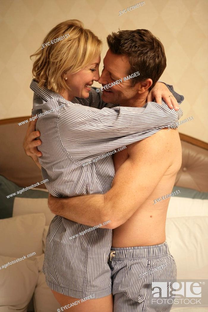Stock Photo: Mature couple in bed hugging each other.