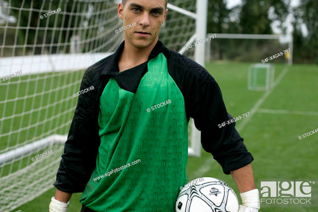Stock Photo: Goalkeeper with ball under his arm standing in front of a goal.