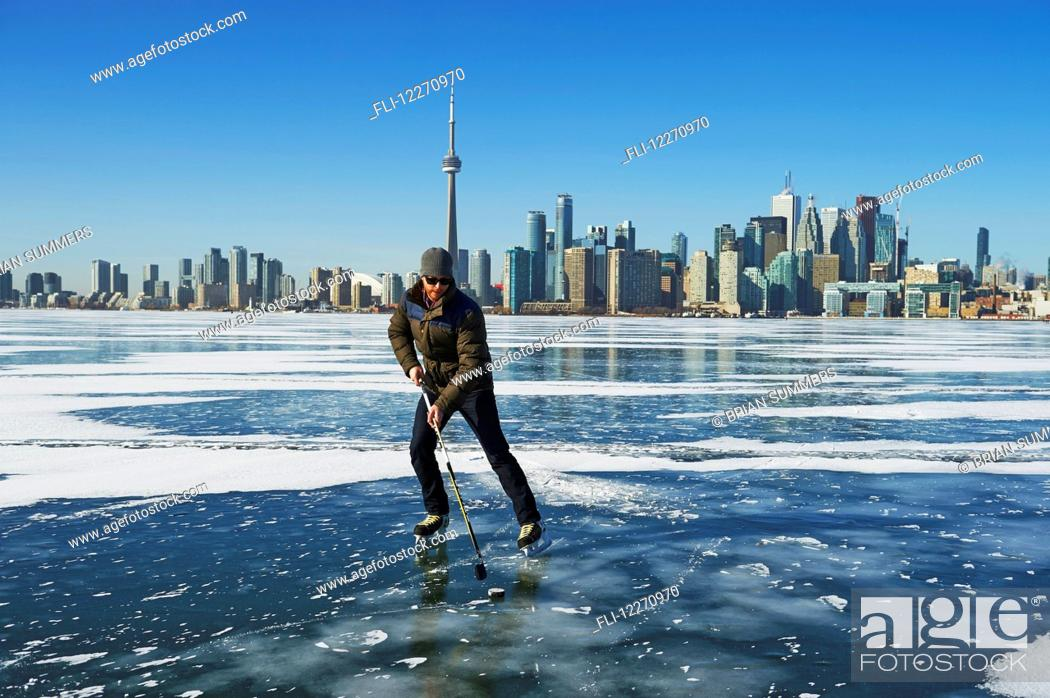 Stock Photo: Hockey player and city skyline from Ward's Island; Toronto, Ontario, Canada.