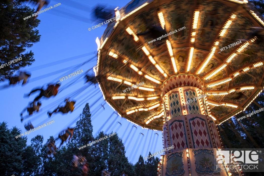 Stock Photo: Flying chairs in the amusement park illuminated at dusk, MADRID, SPAIN, EUROPE.