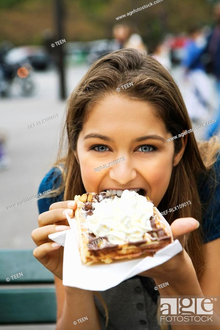 Stock Photo: Young woman eating cream and chocolate covered Waffle, Paris, France.