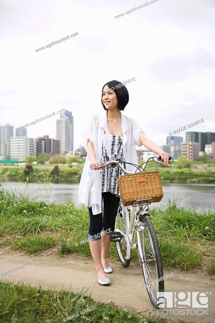Stock Photo: Young woman with bicycle.